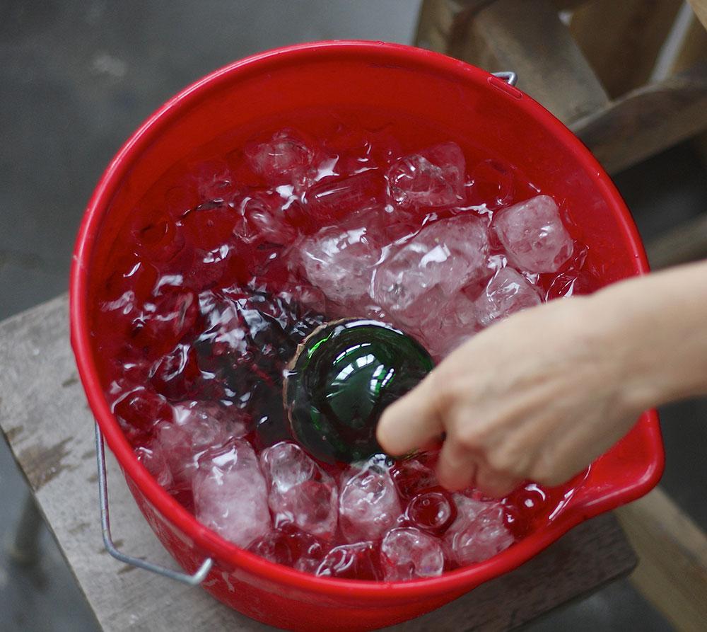 Опускаем нагретую бутылку в ведро с водой и льдом